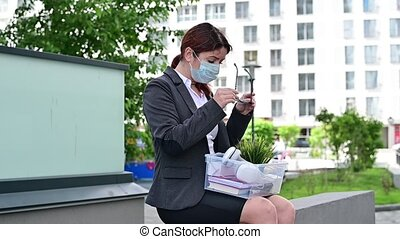 Unhappy fired masked woman sitting on the street with a box ...