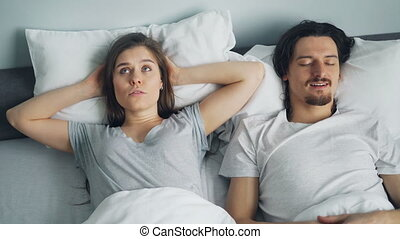 Unhappy girl covering ears with pillow while husband snoring...