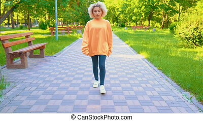 unhappy girl in yellow sweater walking in park - sad and...