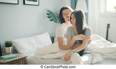 Unhappy girl sitting on bed thinking when guy waking up hugging and kissing