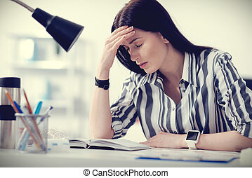 Unhappy gloomy woman holding her forehead