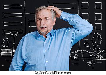 Unhappy grey haired man looking at the car crash