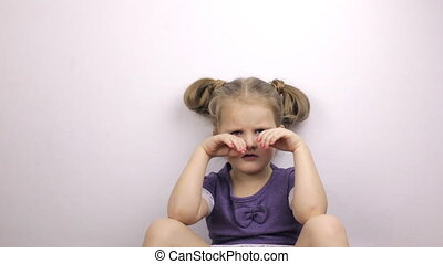 Unhappy little girl rubs her eyes - Unhappy young girl rubs...