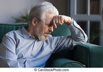 Unhappy lonely grey haired mature man sitting on couch