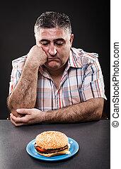 Unhappy man looking at burger