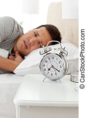 Unhappy man looking at his alarm clock while lying on his bed