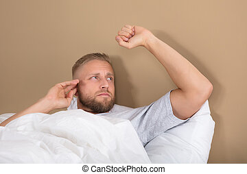 Unhappy Man Lying On Bed