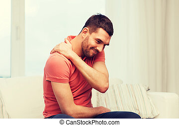 unhappy man suffering from neck pain at home