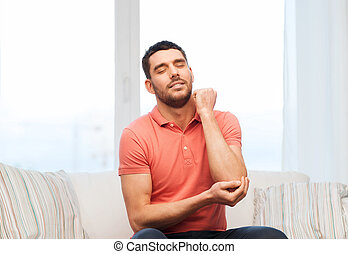 unhappy man suffering from pain in hand at home