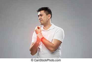 unhappy man suffering from pain in hand