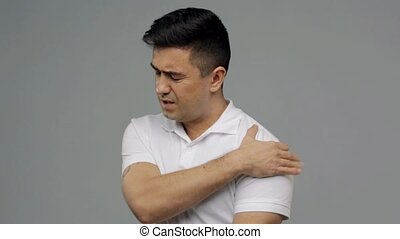 unhappy man suffering from pain in shoulder - people,...