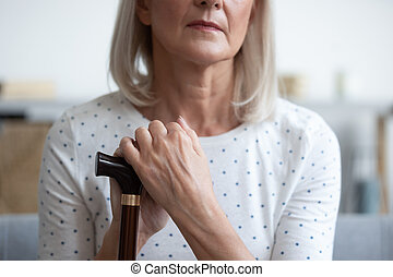 Unhappy mature woman holding hands on walking stick close up