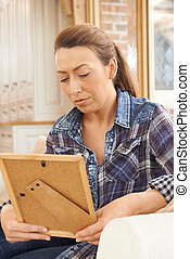 Unhappy Mature Woman Looking At Photograph In Frame