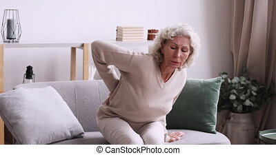 Unhappy middle aged 70s grey haired woman feeling lower lumbago spinal backpain while getting up from couch. Unhealthy senior mature retired grandmother suffering from osteoporosis arthritis.