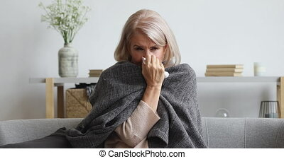 Unhappy middle aged female retiree suffering from flu cold...