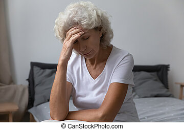 Unhappy middle aged woman suffering from strong morning headache.