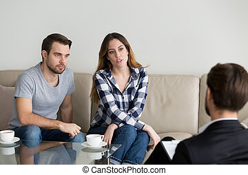 Unhappy millennial couple talking to psychologist sitting on couch