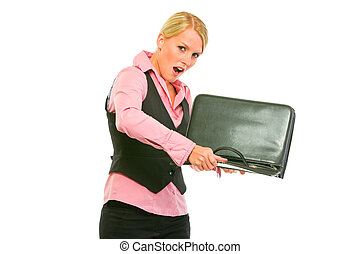 Unhappy modern business woman shaking out something from briefcase