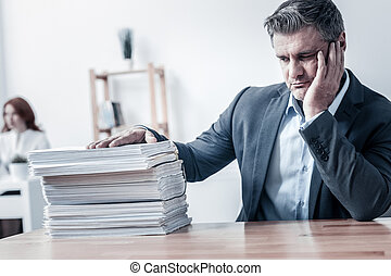 Unhappy office worker looking at pile of documents