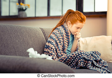 Unhappy red haired girl coughing in her hand