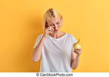 unhappy sad depressed woman cannot to cut onion for preparing food