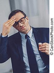 Unhappy sad man touching his forehead