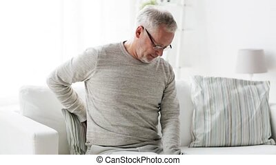 unhappy senior man suffering from backache at home - people,...