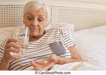 Unhappy senior woman lying in bed taking medicine