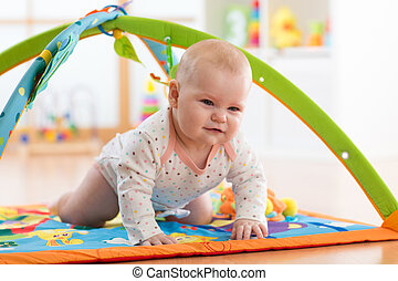 Unhappy seven months baby girl crawling on colorful playmat