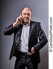 Unhappy stressed angry business man talking on mobile phone very emotional in office suit and looking up on grey studio background. Closeup