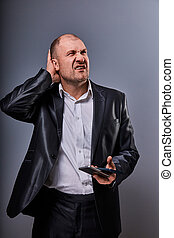 Unhappy stressed tired business man holding two mobile phones in hands and looking up in office suit on grey studio background. Closeup