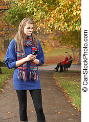 Unhappy Teenage Girl Standing In Autumn Park With Couple On Bench In Background