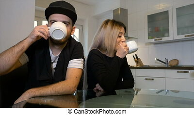 Unhappy upset couple having morning coffee not talking to each other after a fight