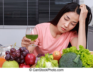 unhappy woman drinking vegetable juice in kitchen