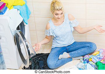 Unhappy woman having a lot of laundry - Confused woman...