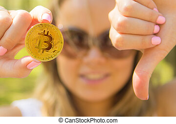 woman holding a golden bitcoin and showing thumbs down