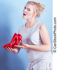 Unhappy woman holding high heels