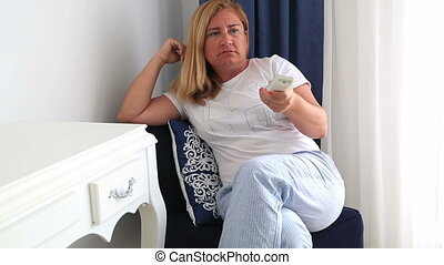 Unhappy woman pressing button of remote controller - Angry...