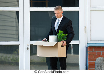 Businessman Carrying His Belongings In Box After Being Fired
