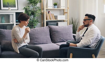 Unhappy young lady crying talking to therapist in psychological clinic