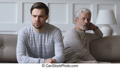 Unhappy young man sitting with older middle aged father on different sides of comfortable couch, ignoring each other after family conflict quarrel argue fight, relationship problems, generations gap.