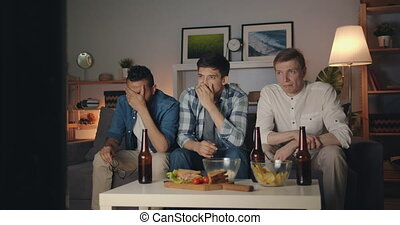 Unhappy young men with sad faces crying watching TV at night...