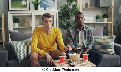 Unhappy young people guys are watching TV with upset faces...