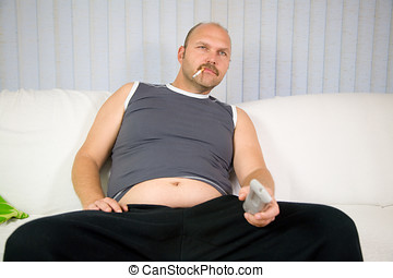 Unhealthy behavior - Overweight man sitting on the couch...