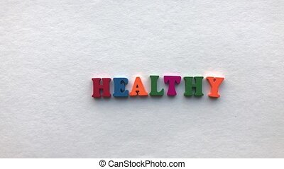 unhealthy. coloured wooden letters on a white sheet of paper