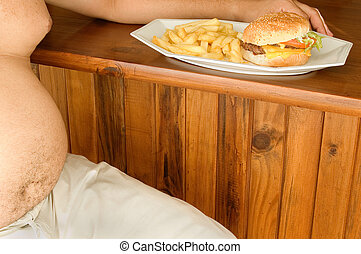 Unhealthy diet - A middle aged man sits next to a burger and...