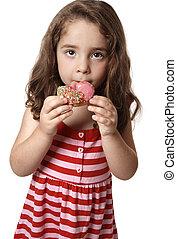 A child eating an unhealthy doughnut snack.