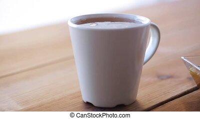 lump sugar falling to cup of tea and splashing