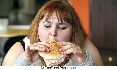 Close up of overweight woman eating a hamburger