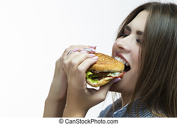 Unhealthy Eating Concepts. Closeup of Caucasian Woman Eating Burger. Profile Face View. Posing in Striped Shirt Indoors in Studio.